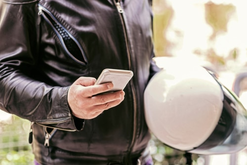 Close up View of Man in Leather Jacket Holding a Sport Helmet and Using a Mobile Phone