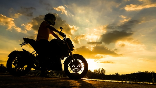 Silhouette of biker with his motorcycle