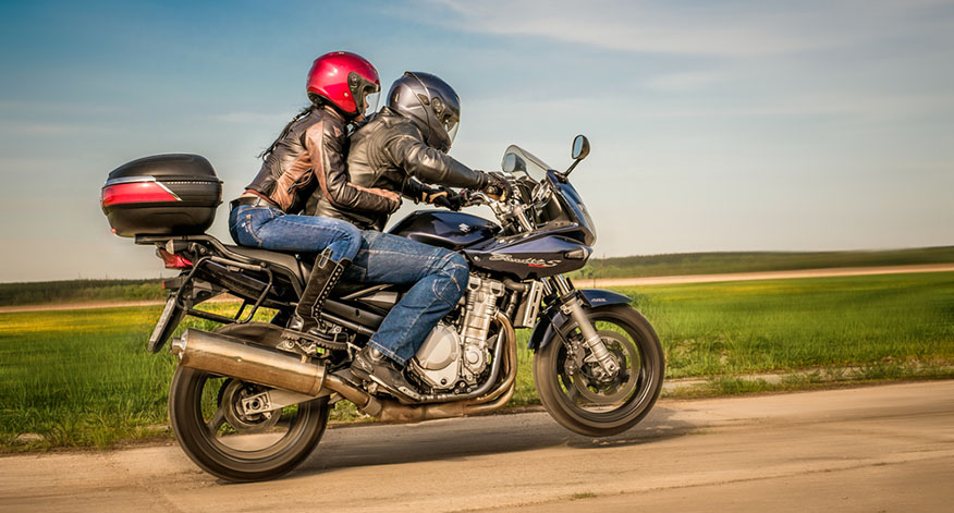 pair riding suzuki motorcycle