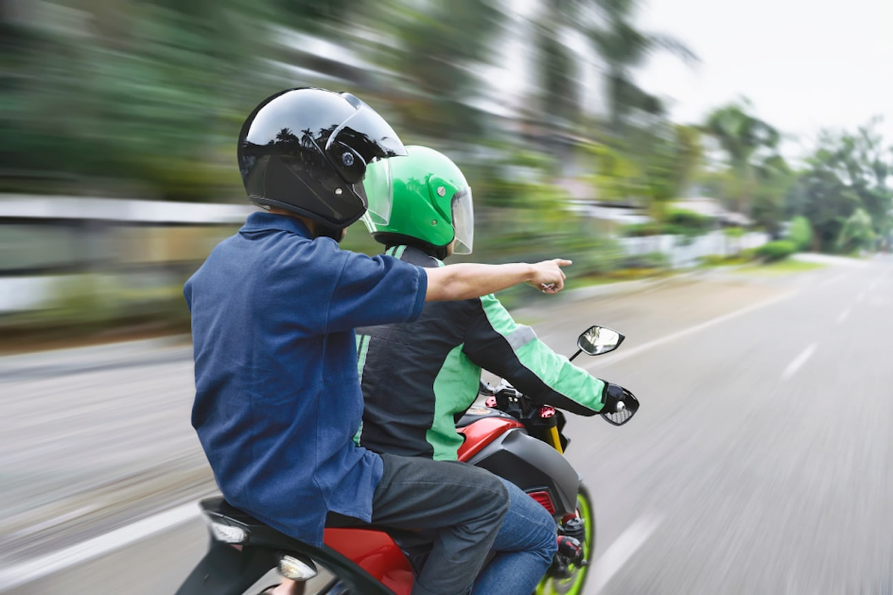 motorcycle passenger pointing ahead