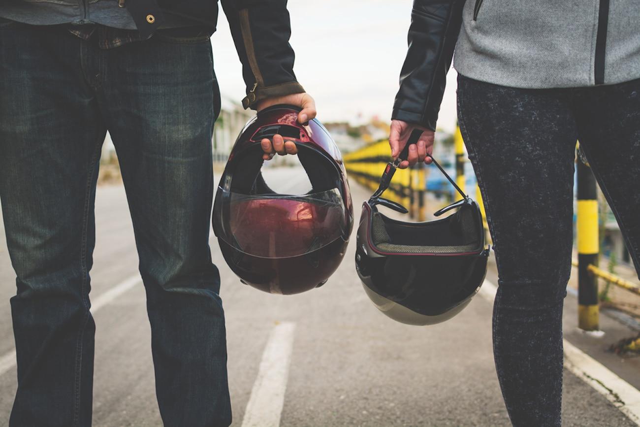 motorcyclists holding helmets