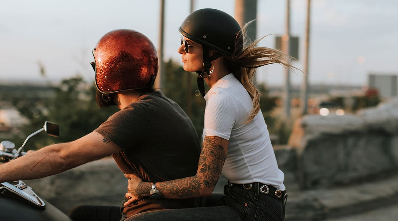 biker couple riding during sunset