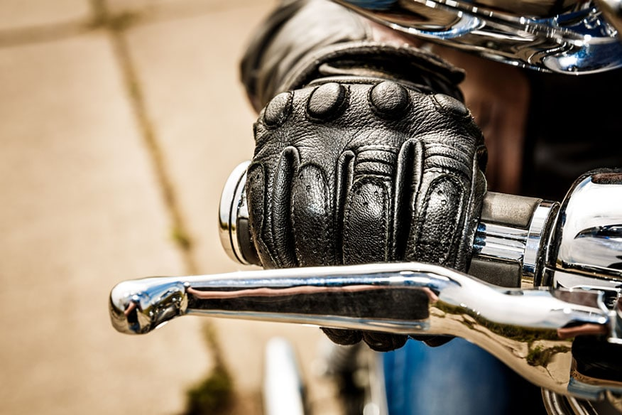 closeup gloved hands motorcycle throttle