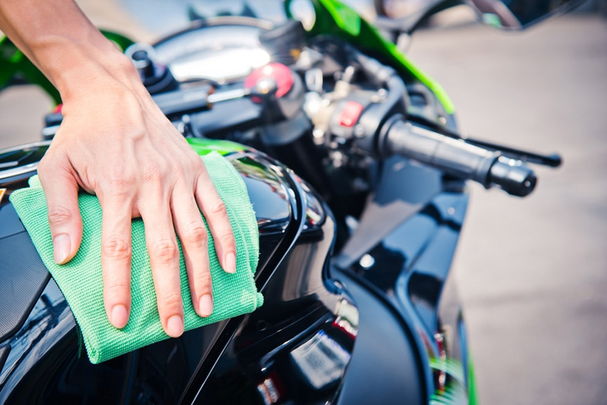 man cleaning motorcycle with green microfiber cloth