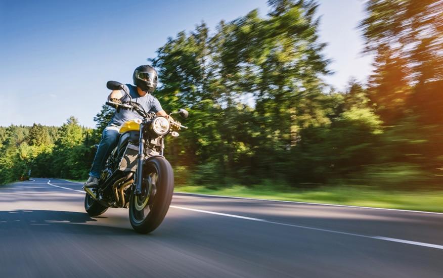modern scrambler motorbike on the forest road riding