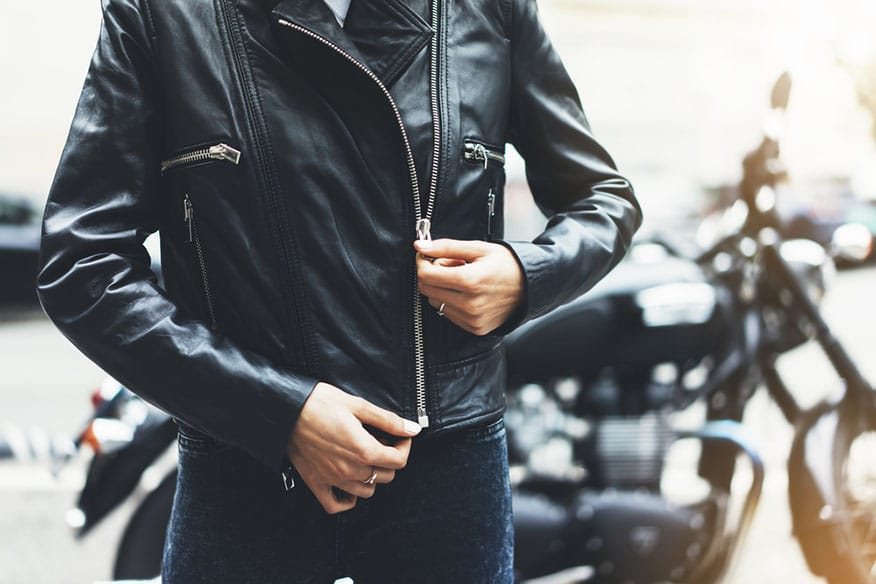 woman unfastening leather jacket
