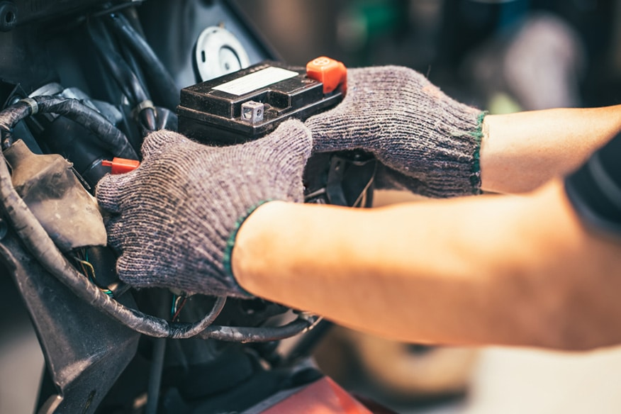 motorcycle mechanic replaces a battery