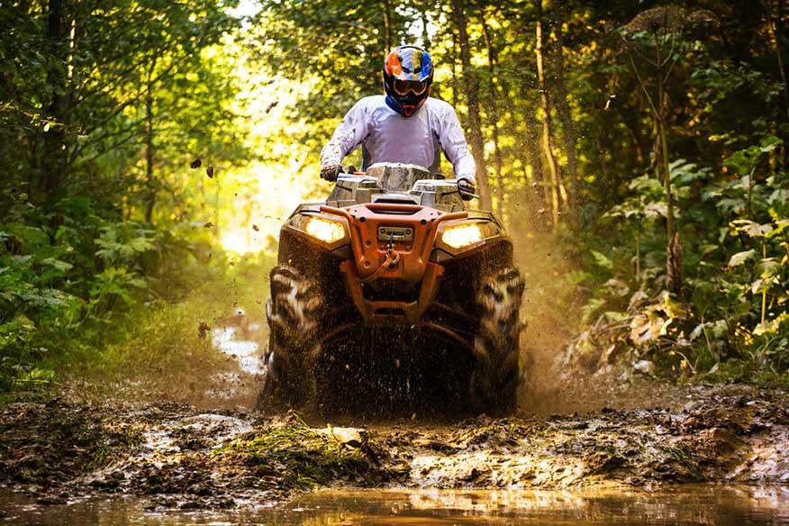 man riding quad in muddy road