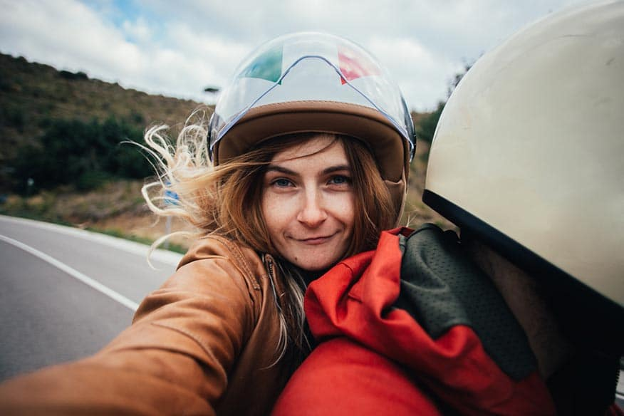 woman takes selfie motorcycle passenger