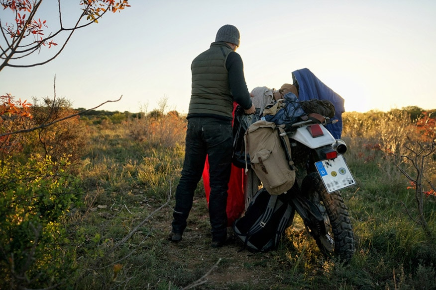 Guy packing up his motorcycle after camping