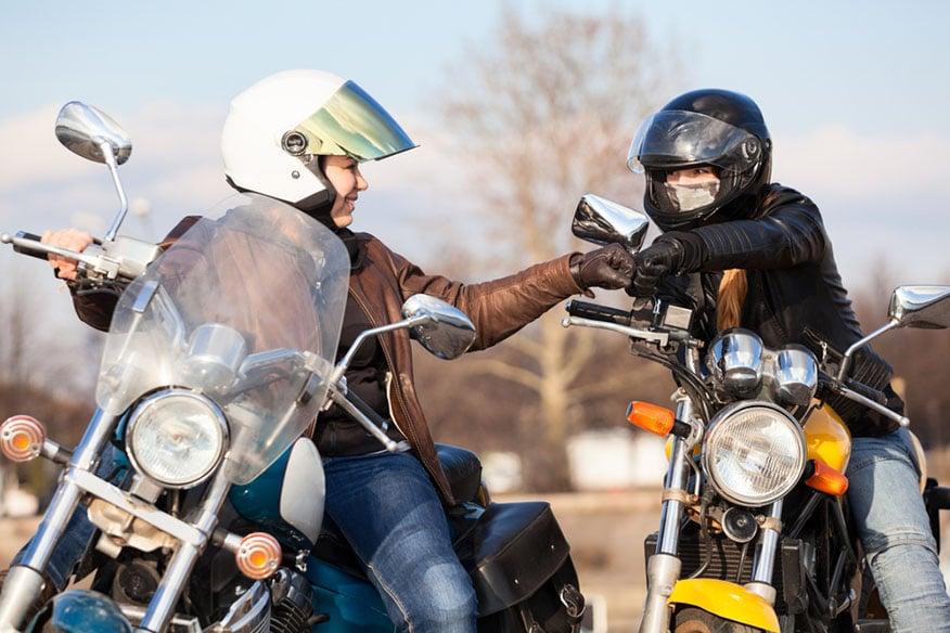 bikers fist bump on road