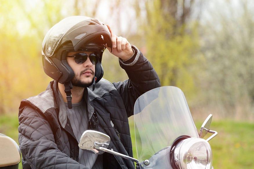 man lifting motorcycle helmet visor