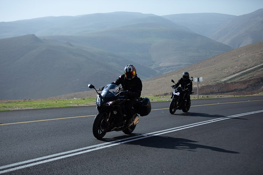 Motorcycle Riders on road by hills