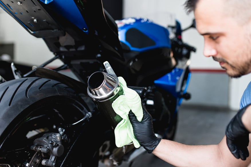 man cleaning motorcycle with cloth
