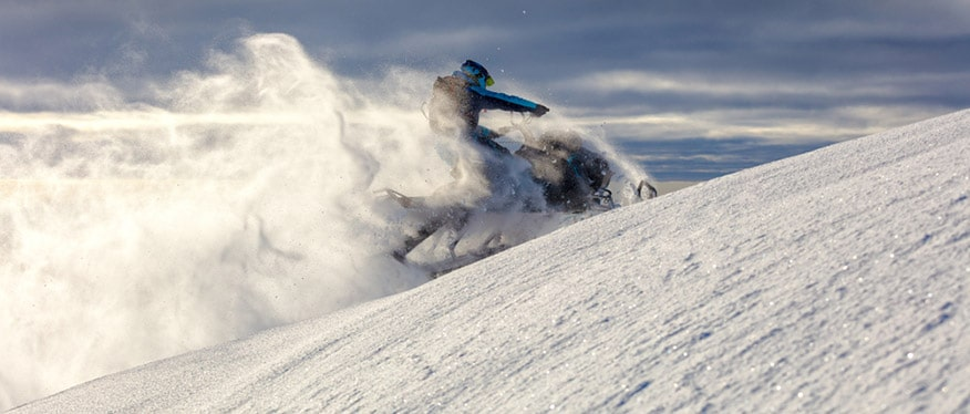 snowmobile rider jumps in a mountain valley