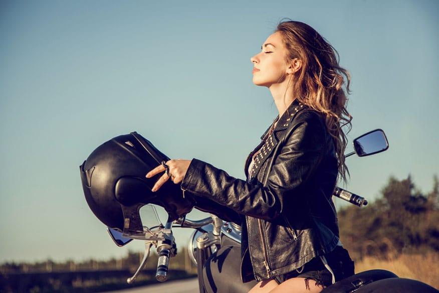 woman placing helmet on head before ride