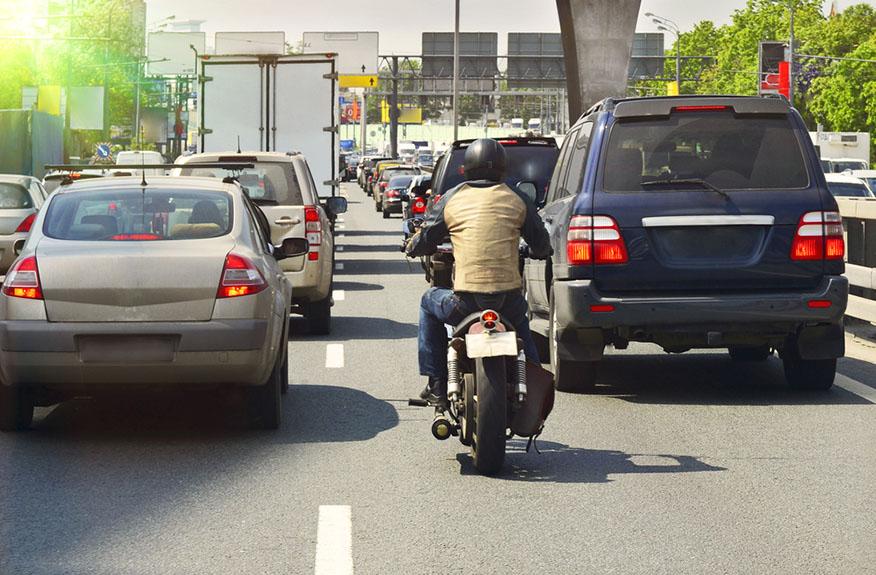 biker between traffic lanes