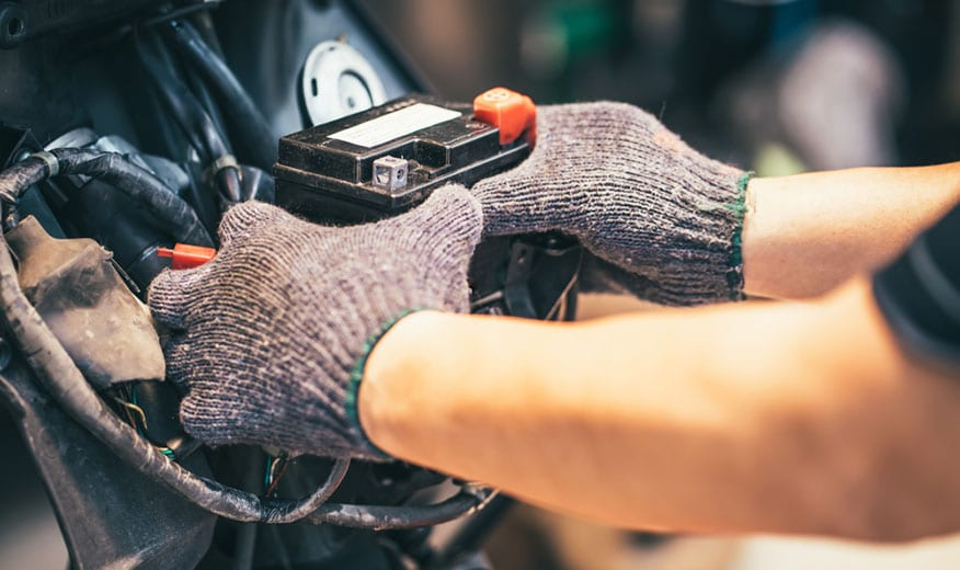 hands placing motorcycle battery
