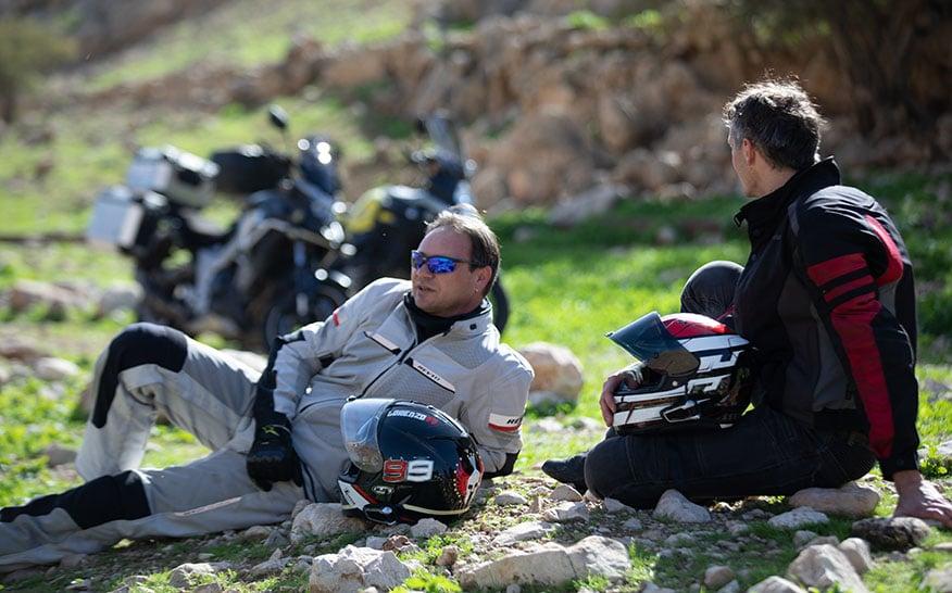 motorcyclists-sit-on-ground-near-bikes