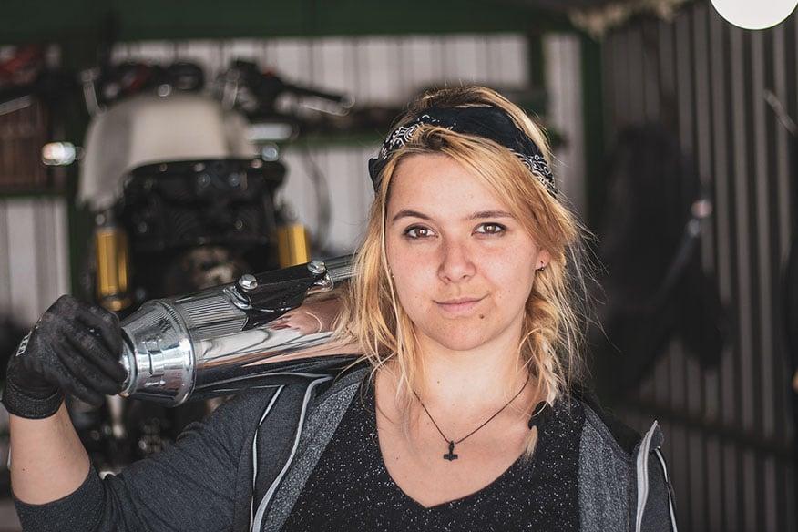 portrait mechanic holding motorcycle part