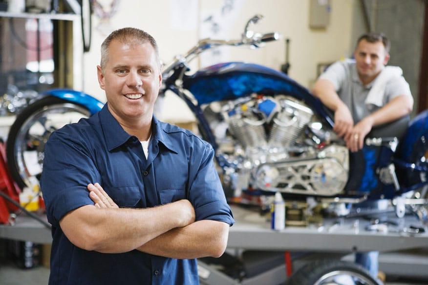 smiling mechanic motorcycle repair shop