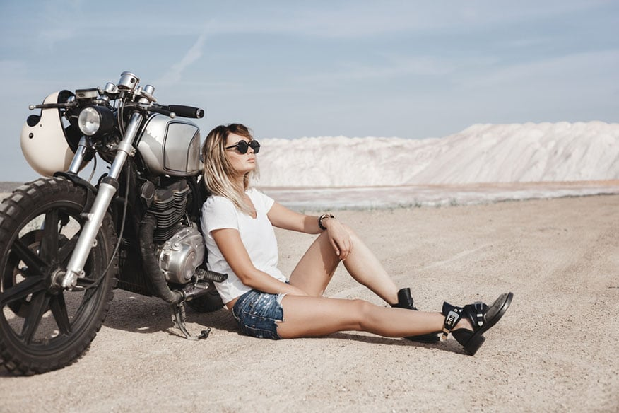woman sitting beside motorcycle
