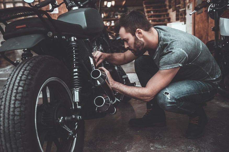Man fixing bike. Confident young man repairing motorcycle near his garage