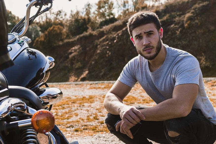 Young biker crouching next to his motorcycle looking at camera