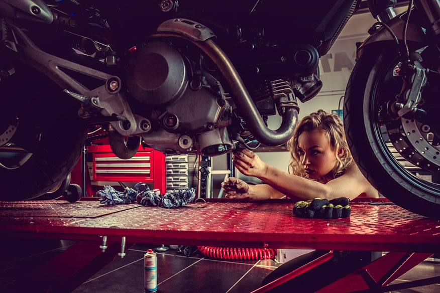 Blonde female repairing motorcycle in a garage.