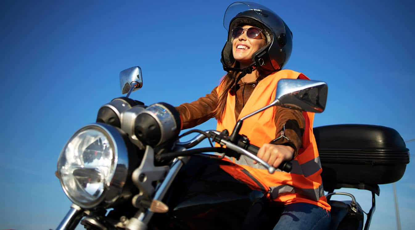 woman in a high visibility vest riding motorcycle