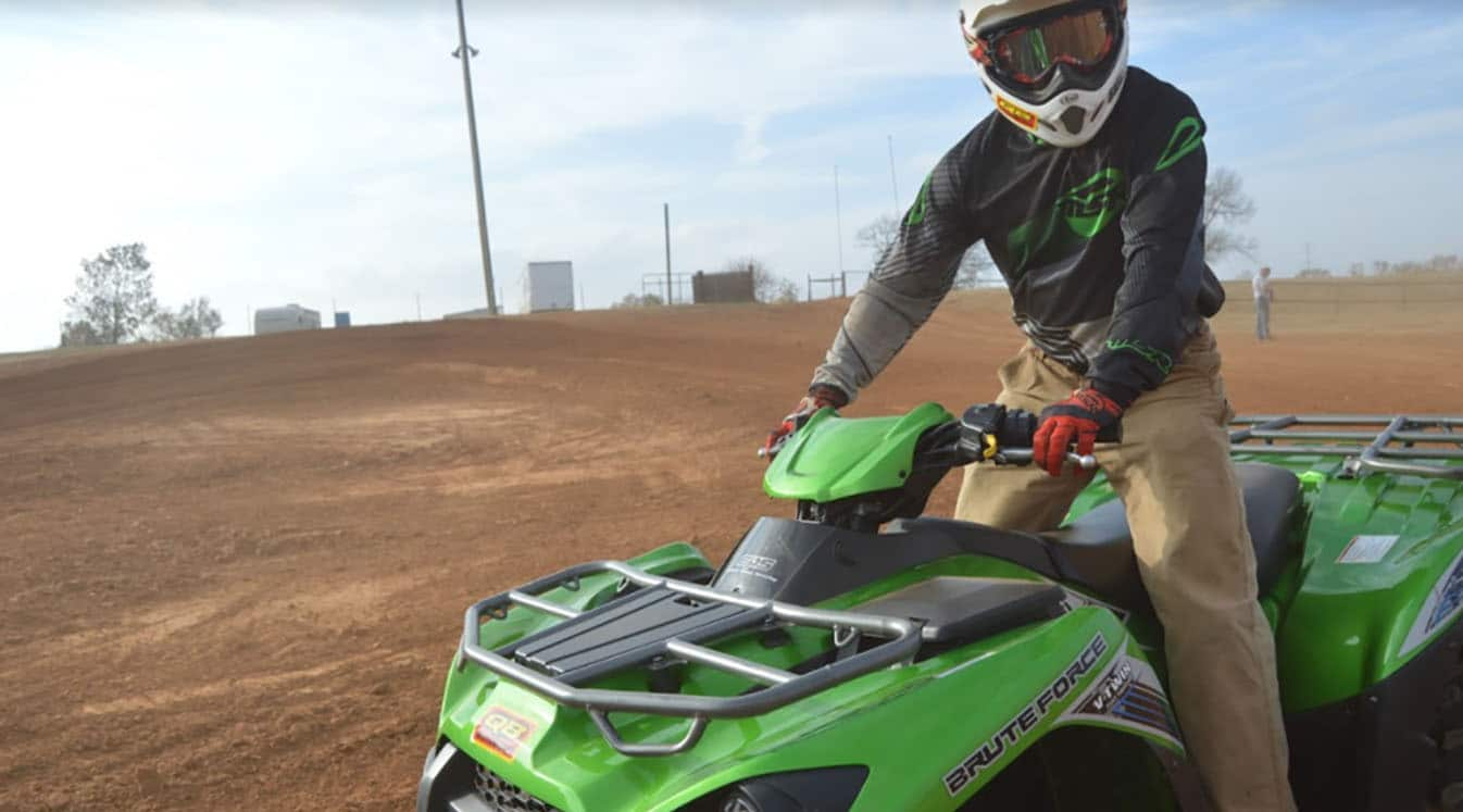 a rider on a green atv in a dirt lot