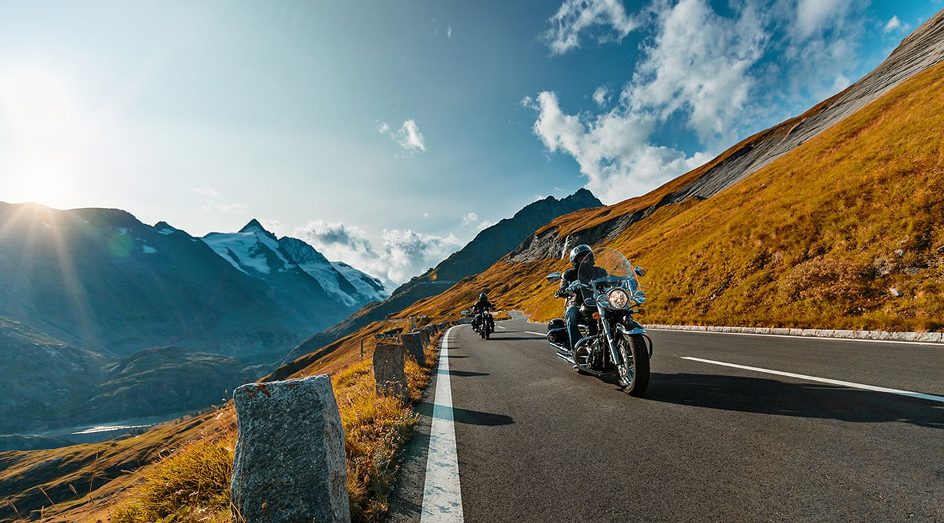 a motorcycle driving riding along an alpine highway