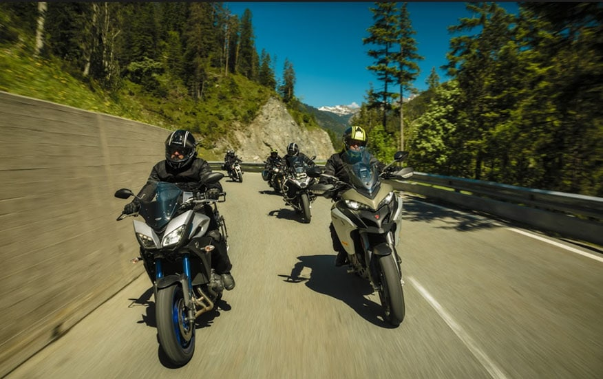 a group of motorcycle riders driving down a mountain road