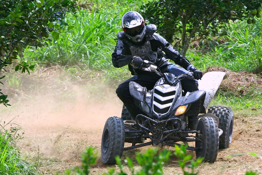 a rider racing an atv on a dirt track