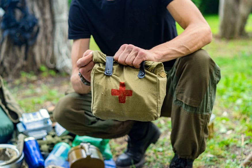a person crouched down holding a first aid kit