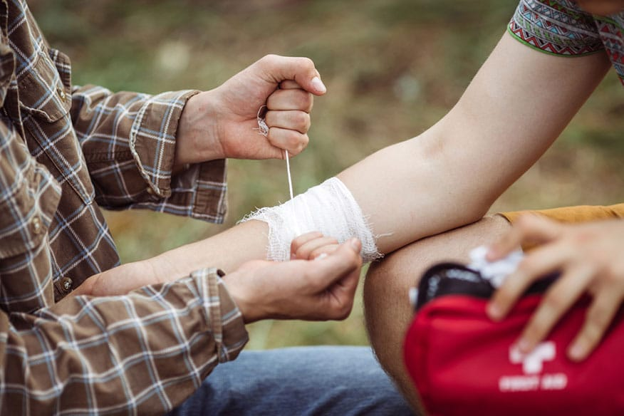 a person wrapping another person's injured arm with gauze