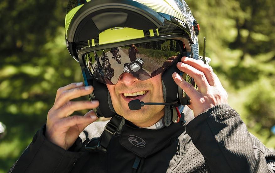 a smiling man adjusting his modular helmet