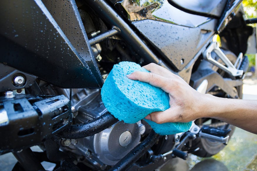 a person washing their motorcycle with a sponge