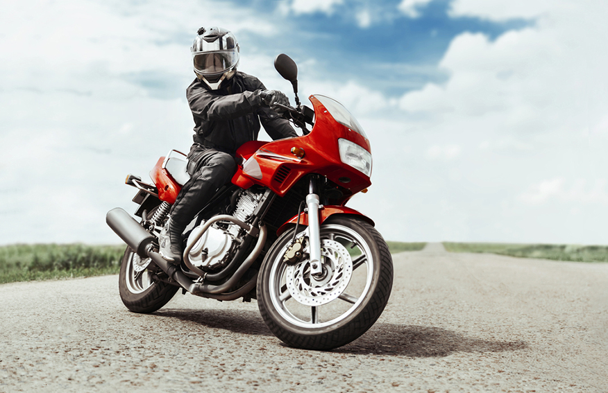 a man sitting on a red motorcycle