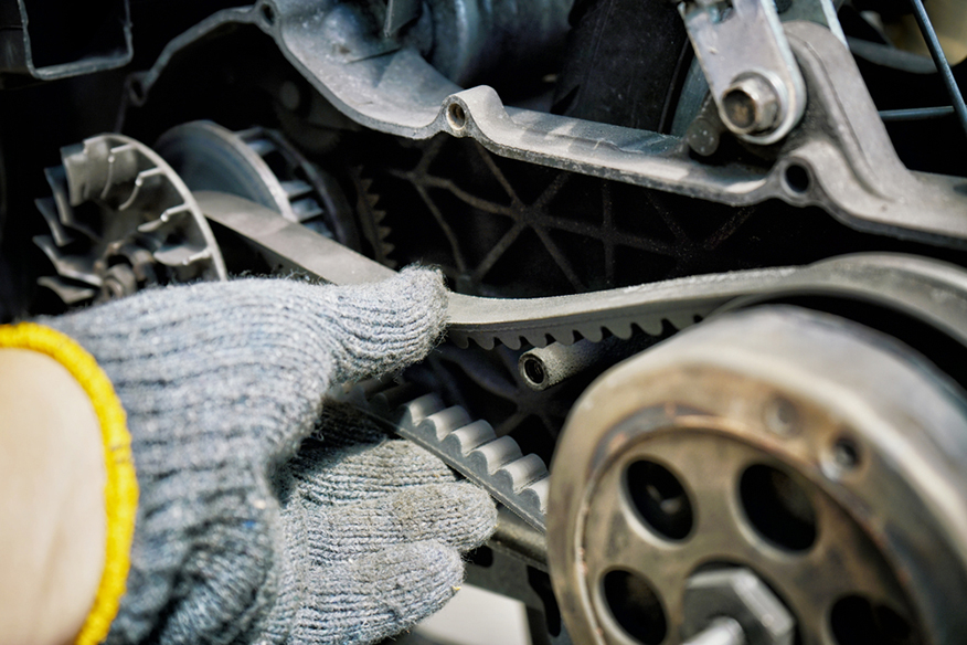 a technician checking the belt tension on a motorcycle