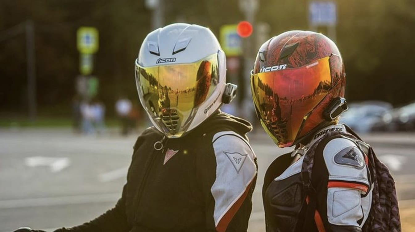 a couple of bikers sitting at an intersection together with clean visors
