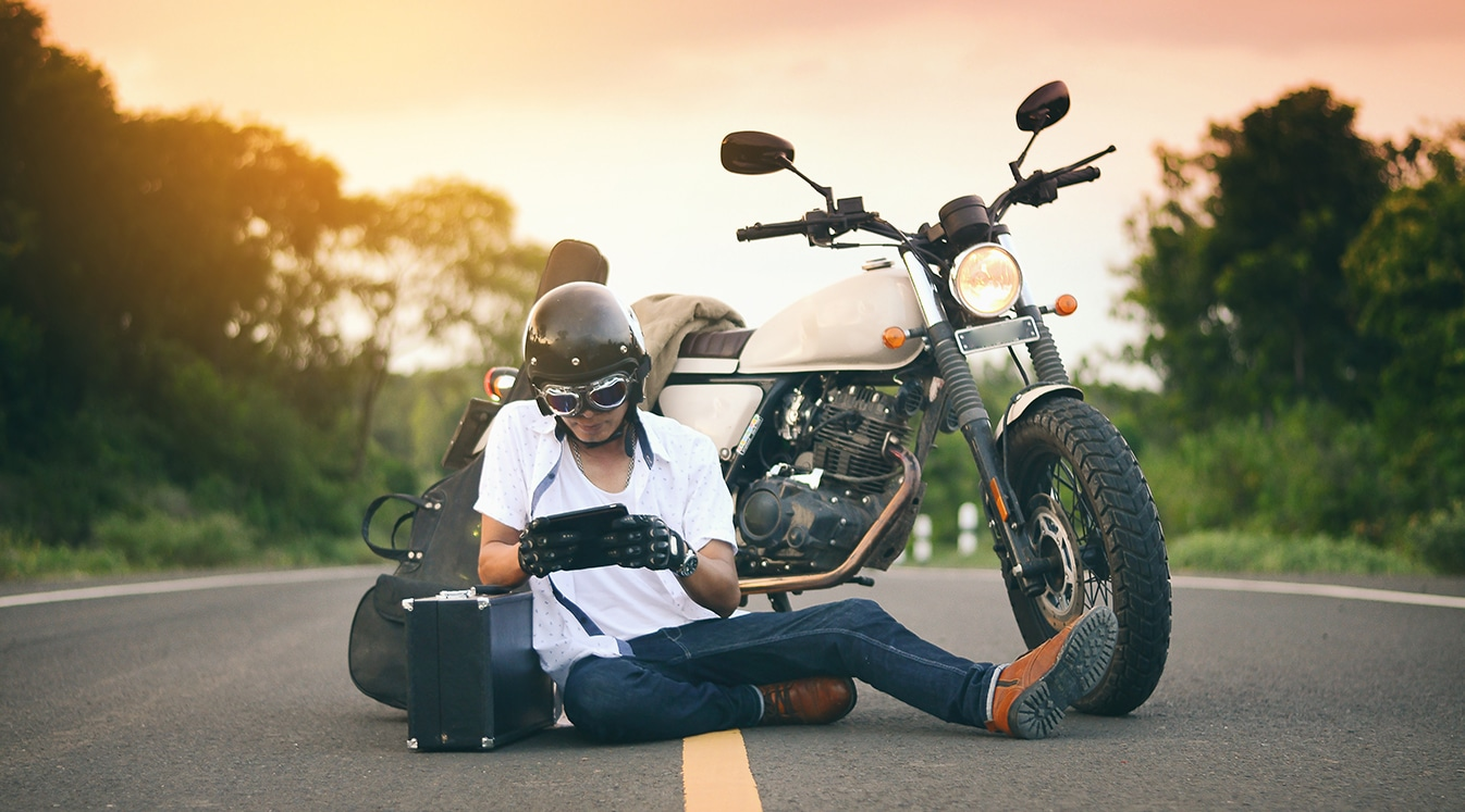 a man sitting in the middle of the road with his motorcycle