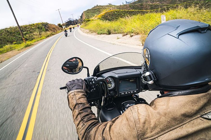 a biker riding down a long stretch of open road