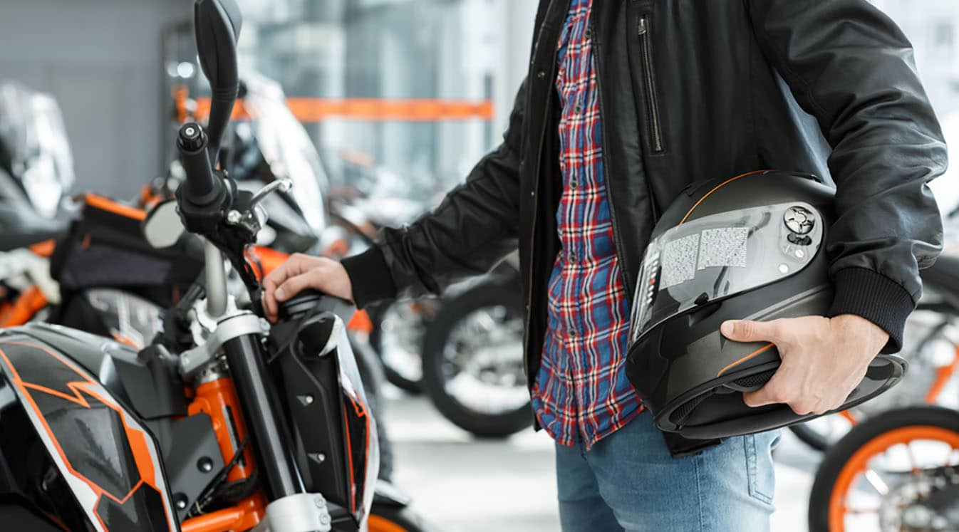 a biker holding a helmet and looking a new motorcycle