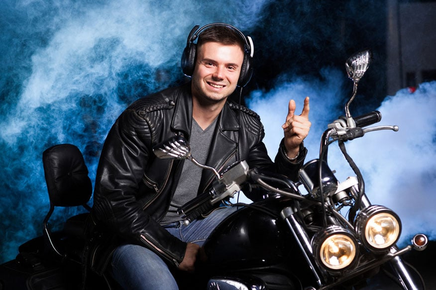 a biker in a leather jacket wearing a headset and sitting on a motorcycle