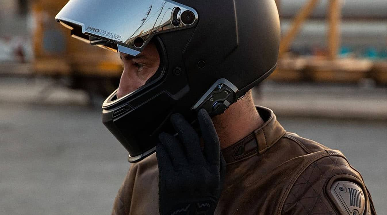 a man using a cardo headset on his motorcycle helmet