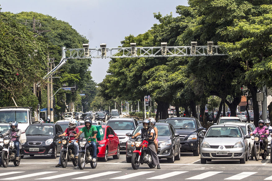 a group of bikers waiting at an intersection