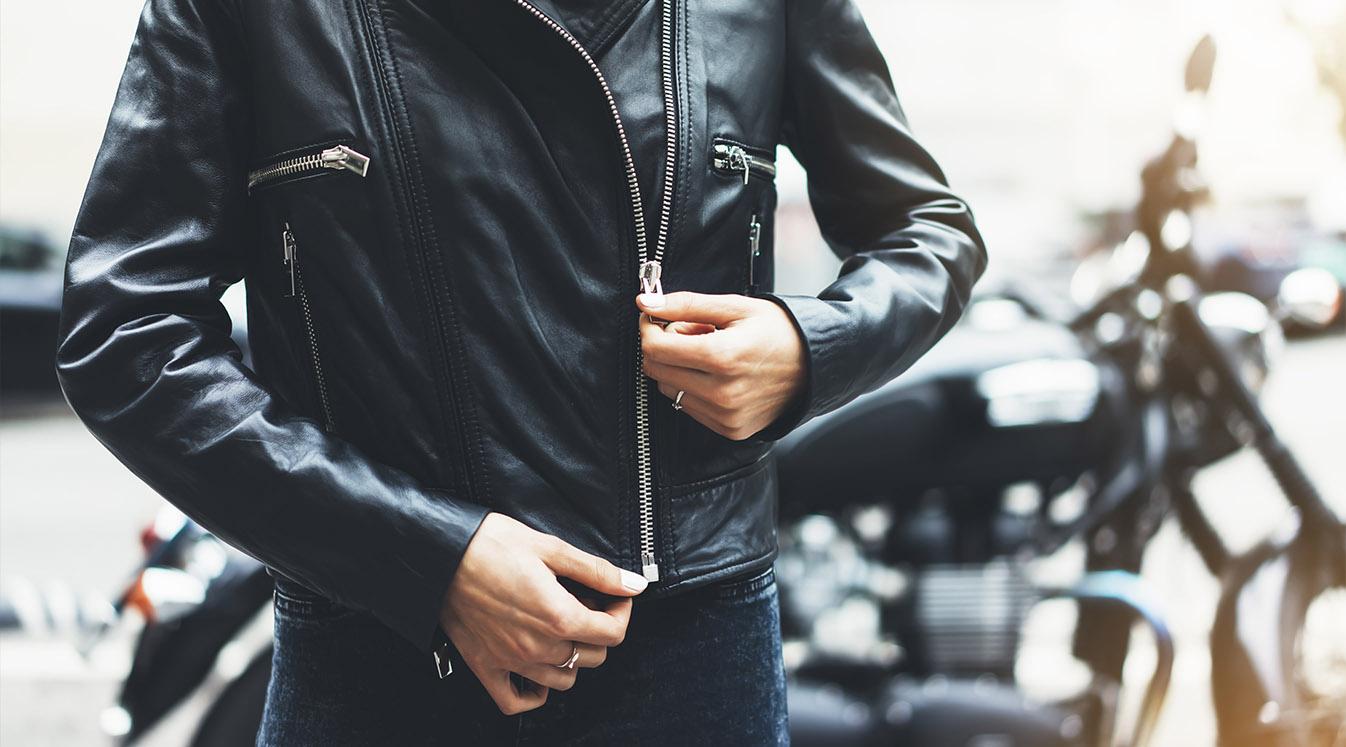 Girl unfastens black leather jacket