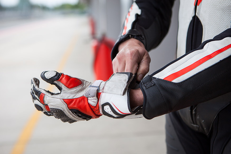 Motorcycle racer puts on a glove before the competition, sports equipment close-up