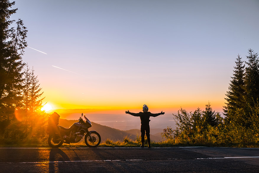 Silhouette of man biker and adventure motorcycle on the road with sunset light. Hands up. enjoy momment. Top of mountains, tourism motorbike, vacation active lifestyle